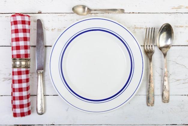 Teller mit silberbesteck auf einem alten tisch Premium Fotos