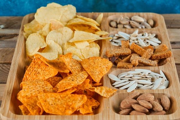 Teller mit verschiedenen snacks auf einem holztisch. chips, cracker, mandeln, pistazien, sonnenblumenkerne. Kostenlose Fotos