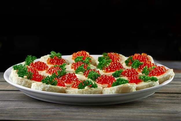 Teller voll von köstlichen roten kaviarbutter-häppchen, die auf holztisch auf schwarzem wand-copyspace serviert werden, der nahrungsmittel-delikatessen-gourmet-meny-kochendes vorspeisenkonzept isst. Kostenlose Fotos