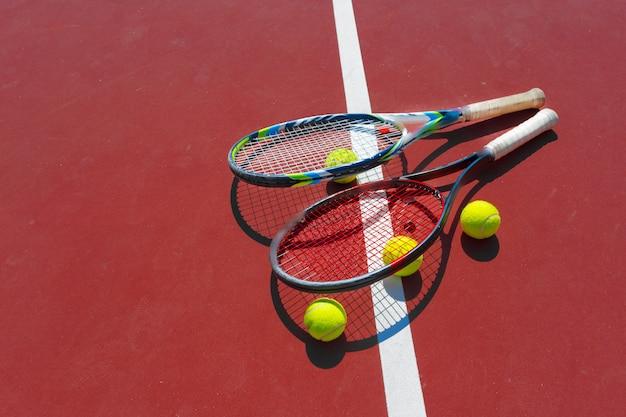 Tennisbälle und schläger auf dem rasenplatz Premium Fotos