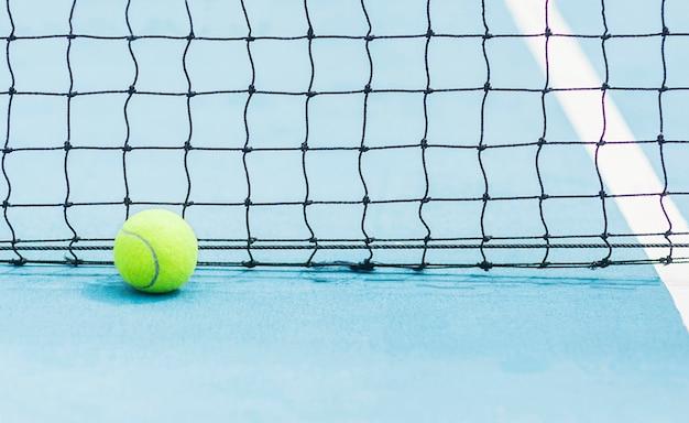 Tennisball mit schwarzem bildschirm net hintergrund auf harten blauen tennisplatz Kostenlose Fotos