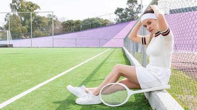 Tennisfrau, die kamera beim sitzen betrachtet Kostenlose Fotos