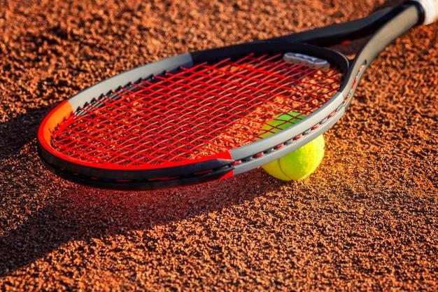 Tennisschläger mit einem ball in der nähe des netzes auf dem irdenen platz. sonniger tag. nahansicht. Premium Fotos