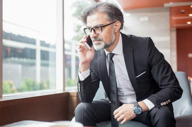 Tensed business man sprechen auf smartphone in der lobby Kostenlose Fotos