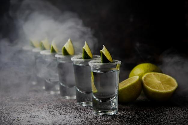 Tequila von der seite in einem glas, serviert mit limetten und salz Kostenlose Fotos