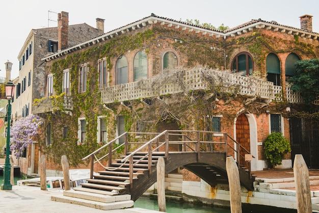 Terrasse in venedig mit blumenterrasse. haus mit einer mit traubenloch bewachsenen fassade. brücke über den venezianischen kanal. Premium Fotos
