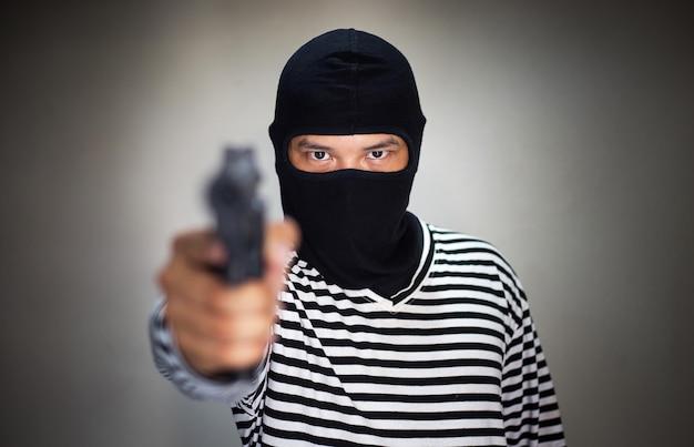 Terroristenmaske und pistole, pistole in der hand halten Premium Fotos
