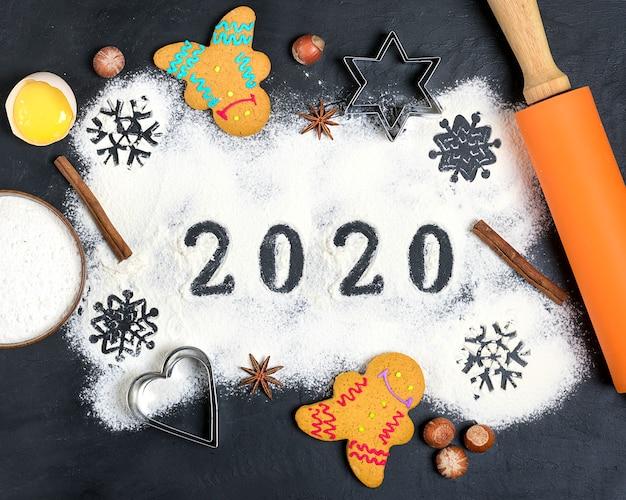 Text 2020 gemacht mit mehl mit dekorationen auf einem schwarzen hintergrund. Premium Fotos