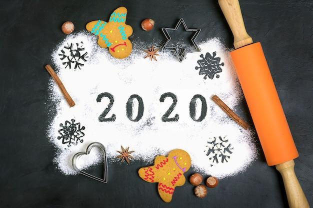 Text 2020 gemacht mit mehl mit dekorationen auf schwarzem. flach liegen. Premium Fotos