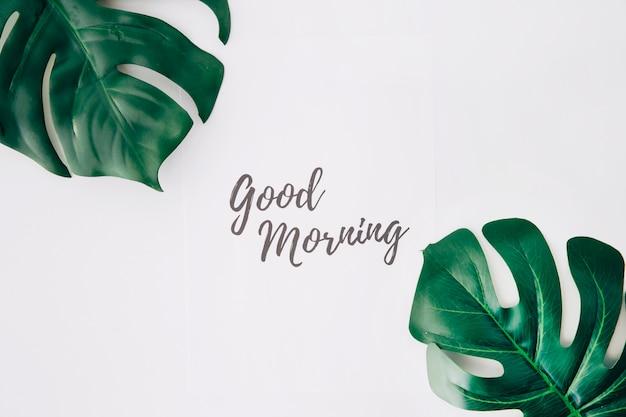 Text des gutenmorgens auf papier nahe dem schweizer käseblatt gegen weißen hintergrund Kostenlose Fotos