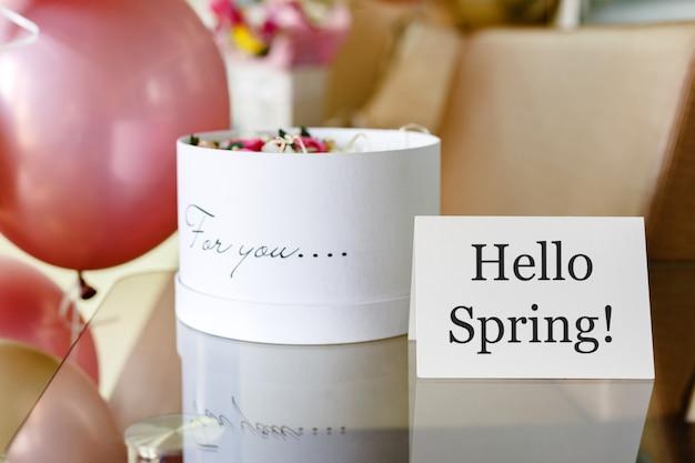 Text hallo frühling auf weißer karte mit blumenkasten. runde schachtel des weißen hutes mit rosa rosenblumen Premium Fotos