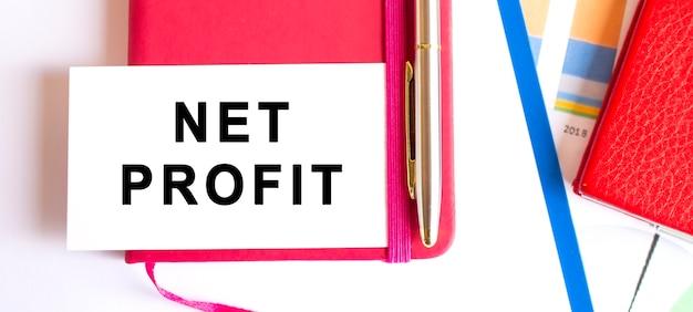 Text net profit auf weißer karte auf notizblock liegend. finanzkonzept. Premium Fotos