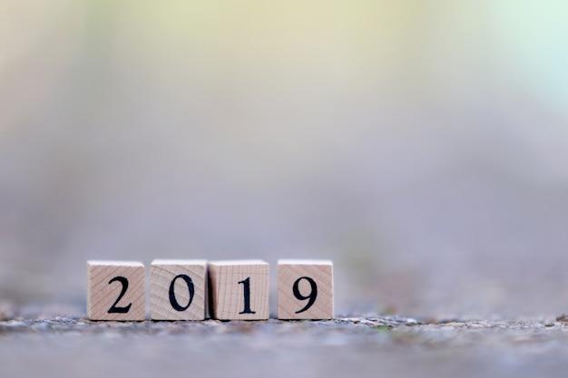 Text-neues jahr 2019 auf hölzernen würfeln auf weichem unschärfe-hintergrund Premium Fotos