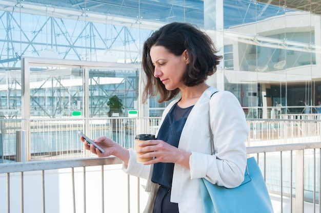 Texting mitteilung der ernsten mittleren erwachsenen geschäftsfrau an der kaffeepause Kostenlose Fotos