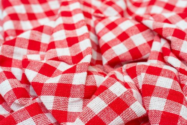 Textur des roten stoffes. rotes kariertes küchentuch. schöne dekorative falten. Premium Fotos