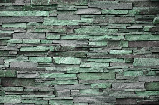 Textur einer steinmauer aus langen und rauen steinen in verschiedenen größen und tönen Premium Fotos