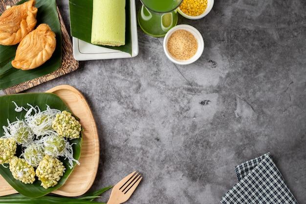 Thailändische süßspeisetabelle mit hühnercurry-hauch, mungobohnereiskrepp und glas kraut Premium Fotos