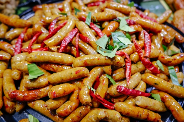 Thailändische würzige kräuterwürste frisch gekocht in einer wanne für verkauf im lokalen markt. Premium Fotos