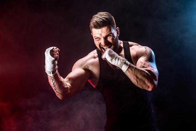 Thailändischer boxer sportlers muay, der auf schwarzer wand mit rauche kämpft. Premium Fotos