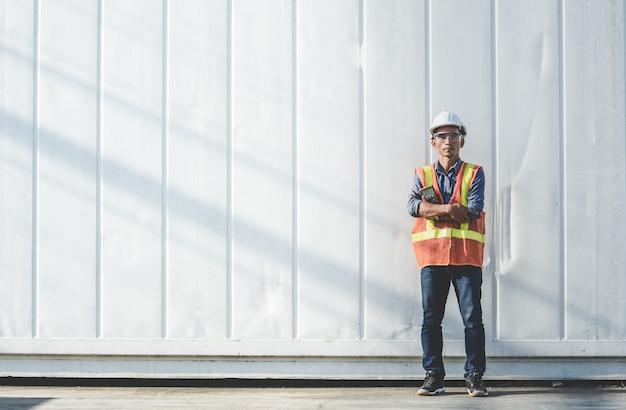 Thailändischer gutaussehender manningenieur, der mit einem meter vor dem behälter steht. Premium Fotos