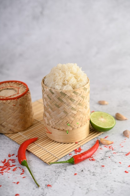 Thailändischer klebriger reis in einem gesponnenen bambuskorb auf einer holzverkleidung mit paprikas, kalk und knoblauch Kostenlose Fotos