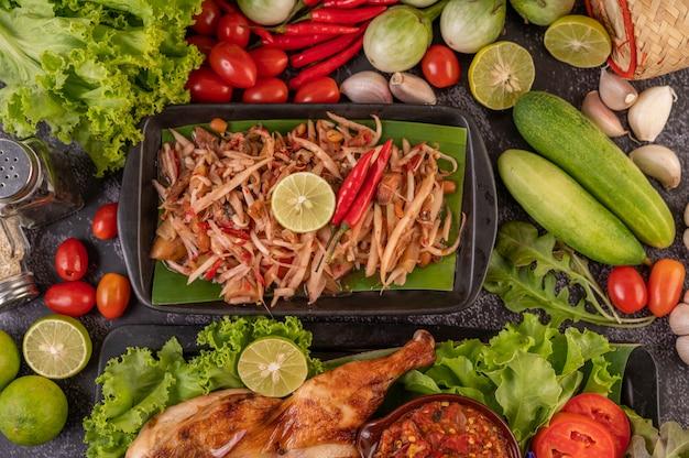 Thailändischer papayasalat in einem schwarzen teller. Kostenlose Fotos