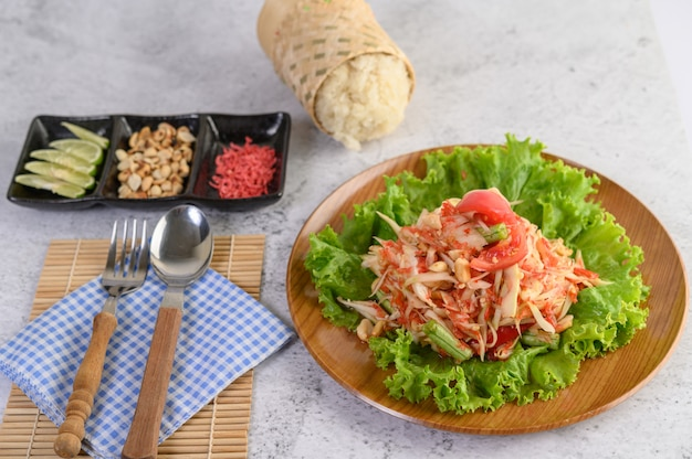 Thailändischer papayasalat in einer hölzernen platte mit klebrigem reis und anderen bestandteilen Kostenlose Fotos