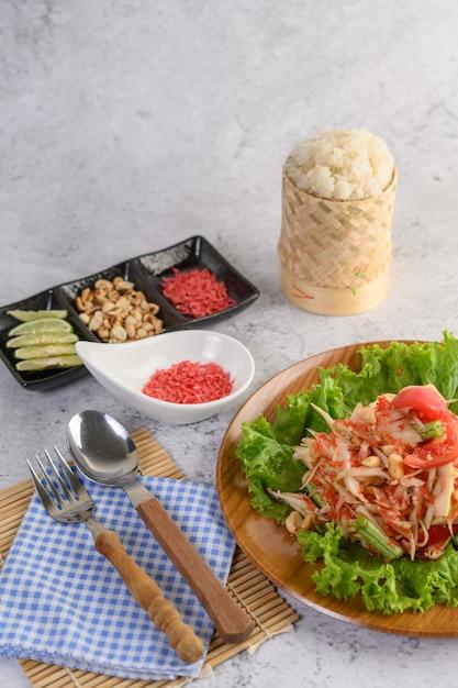 Thailändischer papayasalat in einer hölzernen platte mit klebrigem reis Kostenlose Fotos