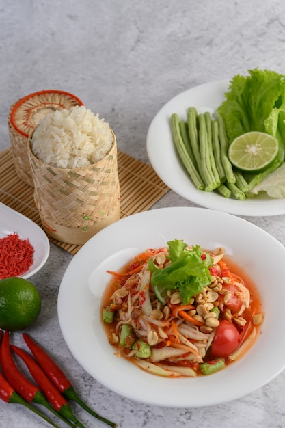 Thailändischer papayasalat in einer weißen platte mit klebrigem reis im weidenkorbbambus und in der getrockneten garnele Kostenlose Fotos
