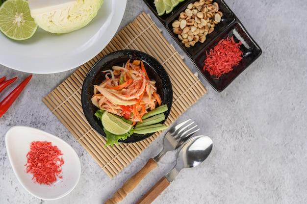 Thailändischer papayasalat in einer weißen platte mit klebrigem reis und getrockneten garnelen Kostenlose Fotos