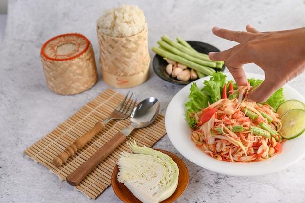 Thailändischer papayasalat in einer weißen platte mit klebrigem reis Kostenlose Fotos