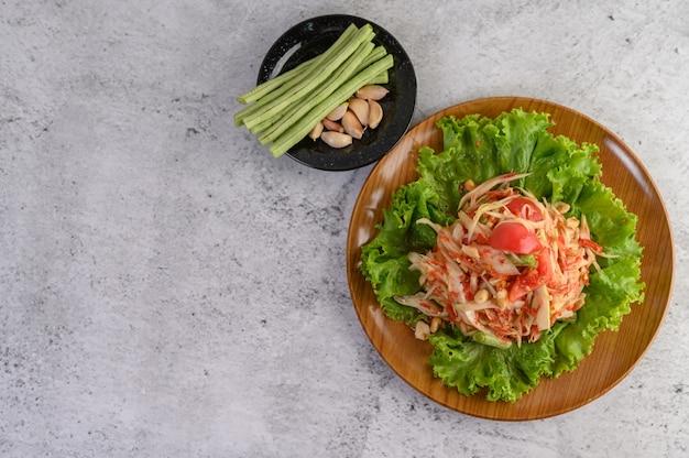Thailändischer papayasalat in einer weißen platte mit yardlong bohnen, knoblauch und weißem kohl Kostenlose Fotos