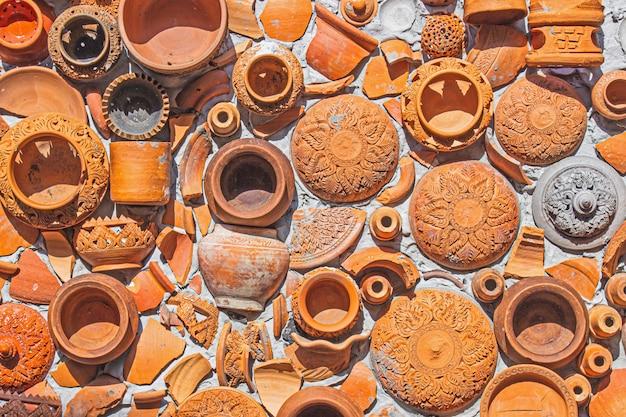 Thailändischer und brauner beschaffenheitshintergrund der nahaufnahme-tonwaren auf wand für innen- oder außendekoration. Premium Fotos
