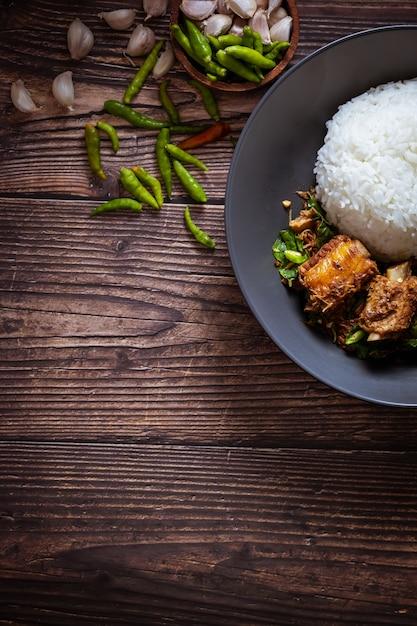 Thailändisches essen, reis garniert mit gebratenem basilikum und schweinefleischknochen. Premium Fotos