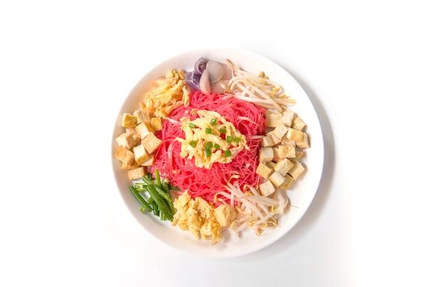 Thailändisches lebensmittel, angebratene nudel mit kokosmilch auf weißem hintergrund Premium Fotos
