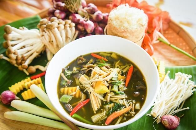 Thailändisches lebensmittel der bambussprosssuppen- und -pilzkräuter- und -gewürzbestandteile diente auf tabelle mit klebrigem reis. Premium Fotos