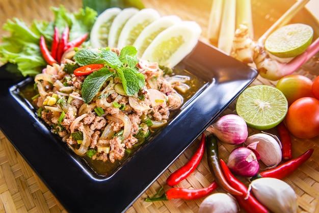 Thailändisches lebensmittel des würzigen gehackten schweinefleischsalats diente auf tabelle mit kräutern und gewürzbestandteilen. Premium Fotos
