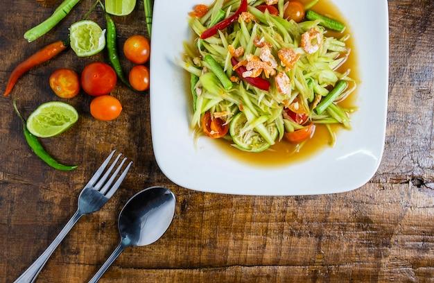 Thailändisches lebensmittel, papayasalat und tomaten, pfeffer und gewürze auf einem holztisch Premium Fotos