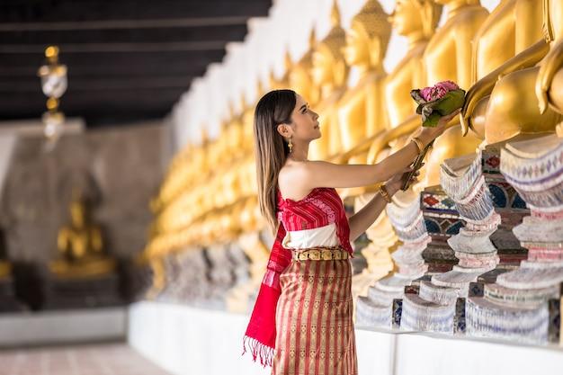 Thailändisches mädchen in der traditionellen thailändischen kostümhand, die lotos im thailändischen tempel, identitätskultur von thailand hält. Premium Fotos