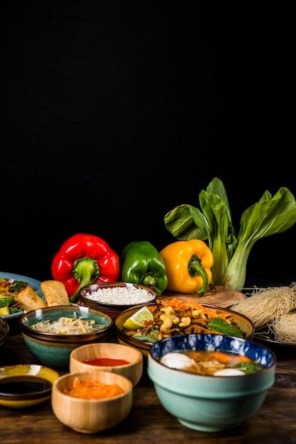 Thailändisches traditionelles lebensmittel mit grünem pfeffer und bokchoy über tabelle gegen schwarzen hintergrund Kostenlose Fotos