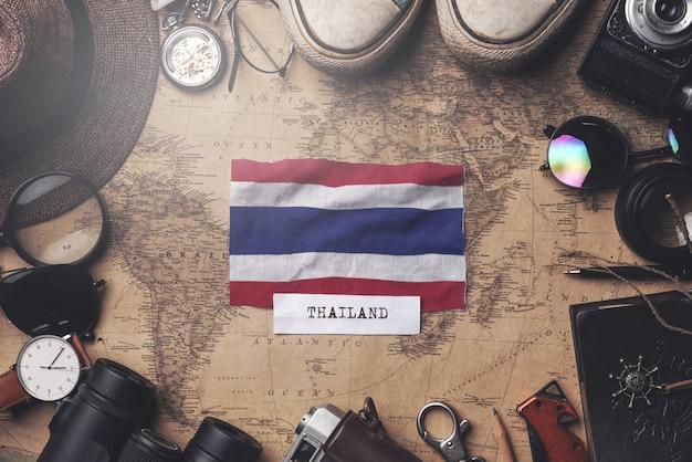 Thailand-flagge zwischen dem zubehör des reisenden auf alter weinlese-karte. obenliegender schuss Premium Fotos
