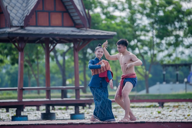 Thailand-frauen und -mann im thailändischen tanz des nationalen kostüms Kostenlose Fotos