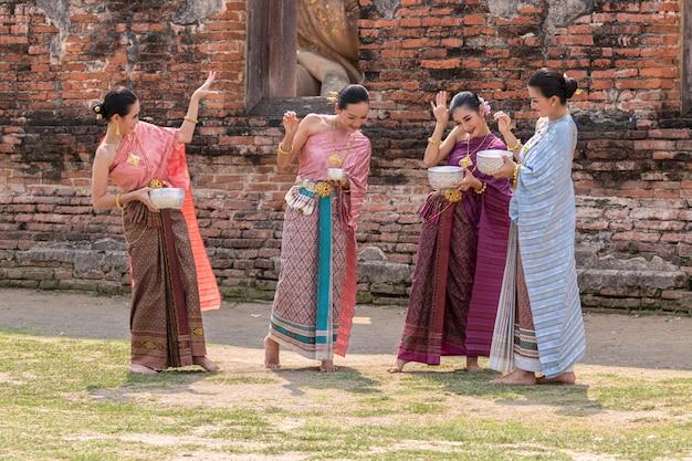 Thailand-kultur. thailändische mädchen und thailändische frauen, die spritzwasser spielen Premium Fotos