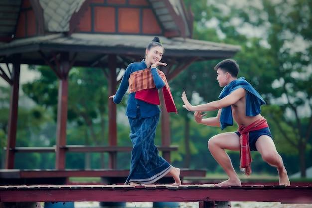 Thailand-tanzenfrauen und -mann im nationalen artkleiderkostüm: thailand-tanz Kostenlose Fotos