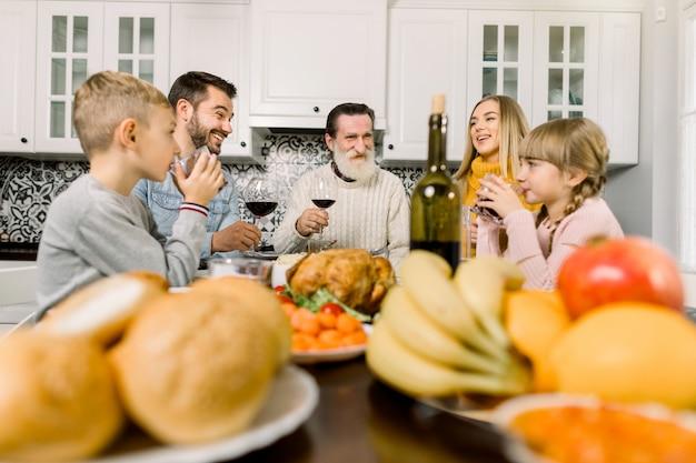 Thanksgiving-feier-konzept. glückliche lächelnde familie, die gläser wein und saft am feiertagsdinner klirrt Premium Fotos