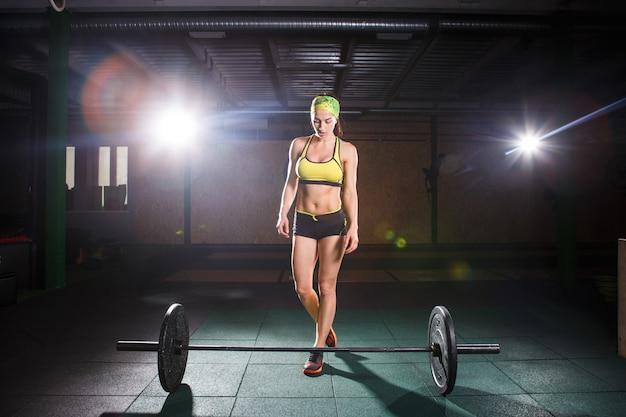 Thema bodybuilding und training für schönen körper, fitness. ein starkes mädchen macht eine übung mit der langhantel Premium Fotos