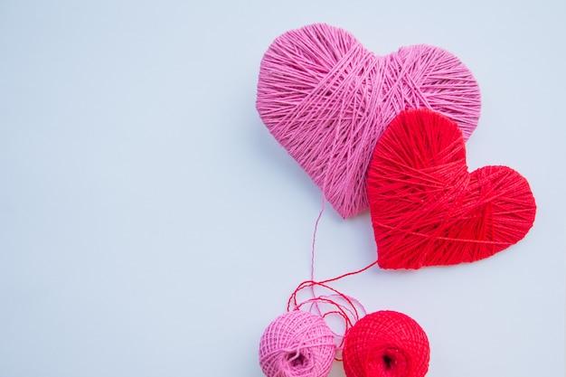 Themenorientiertes stillleben des valentinstags mit liebesherzen. für immer zusammen. bunte garnbälle lokalisiert. Premium Fotos