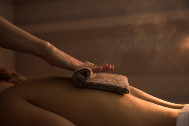 Therapeut, der die rückseite der frau mit heißem tuch im badekurort massiert Kostenlose Fotos