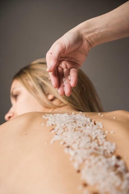 Therapeut, der salz auf der rückseite der jungen frau anwendet Kostenlose Fotos