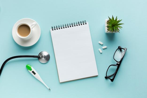 Thermometer; kaffeetasse; stethoskop mit spiralblock; pillen und brillen über blaue fläche Kostenlose Fotos
